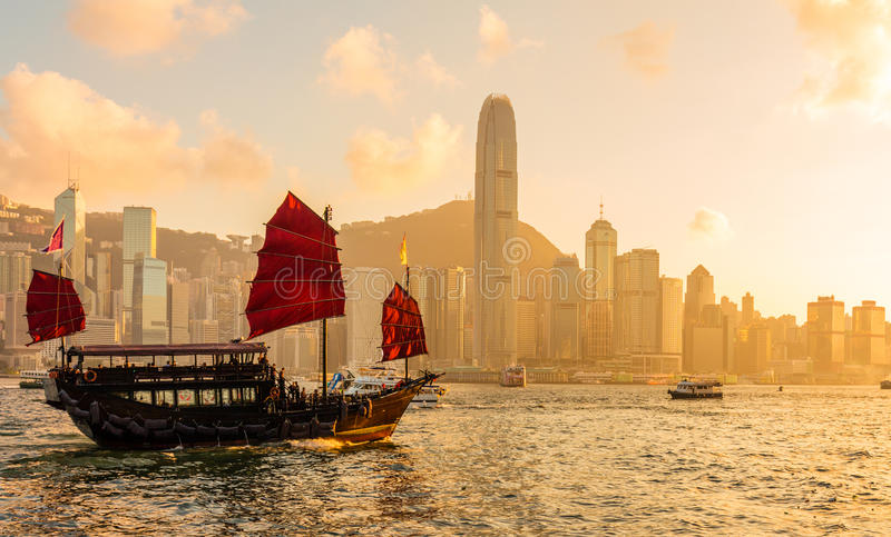 Chinese wooden red sails ship in Hong Kong Victoria harbor at sunset time. Asian young woman stock photos