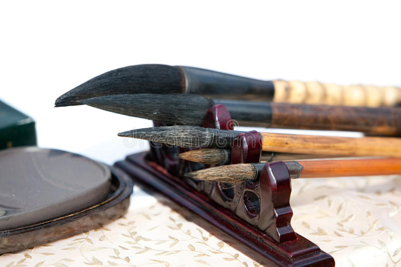 Chinese writing brushes and inkstone. On the table, these is two tools of Four Treasures of the Study in Chinese whick is an expression used to denote the brush stock photos