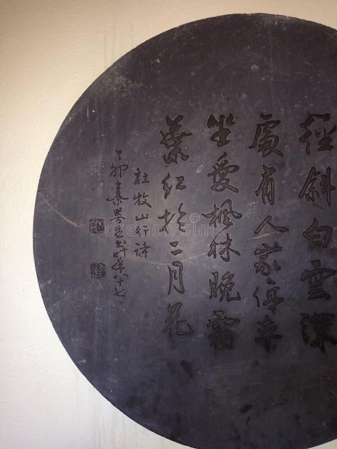 Chinese writing script metallic disc. Wall disc engraving Chinese characters writing script art etching royalty free stock image