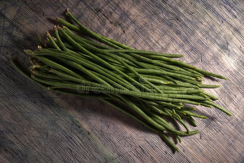 Chinese yard-long long beans bundle. Closeup on rustic wood surface stock photo