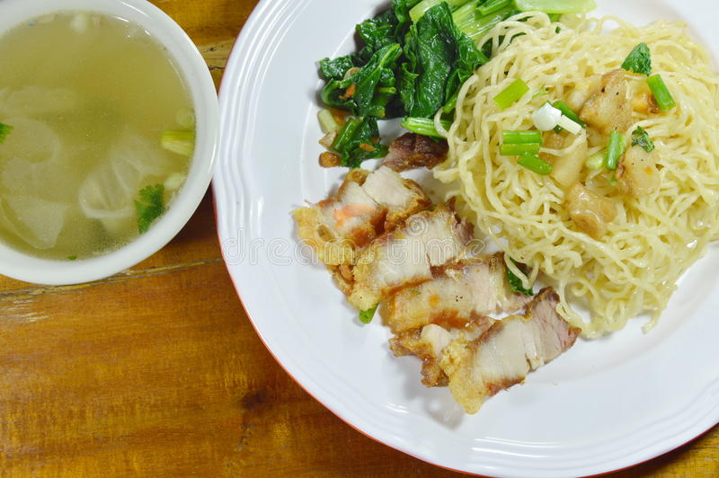 Chinese yellow noodles topping crispy pork on plate with soup royalty free stock image