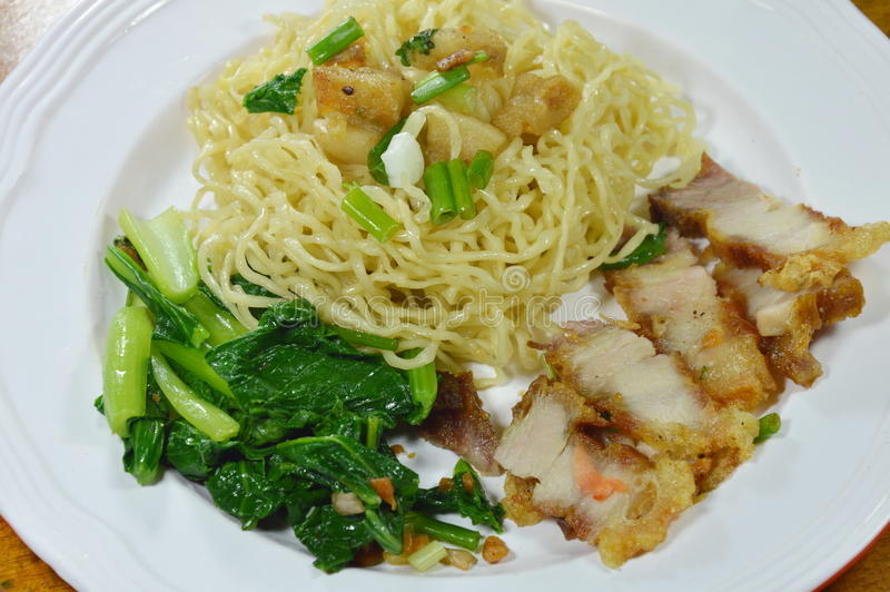 Chinese yellow noodles topping crispy pork on plate royalty free stock image