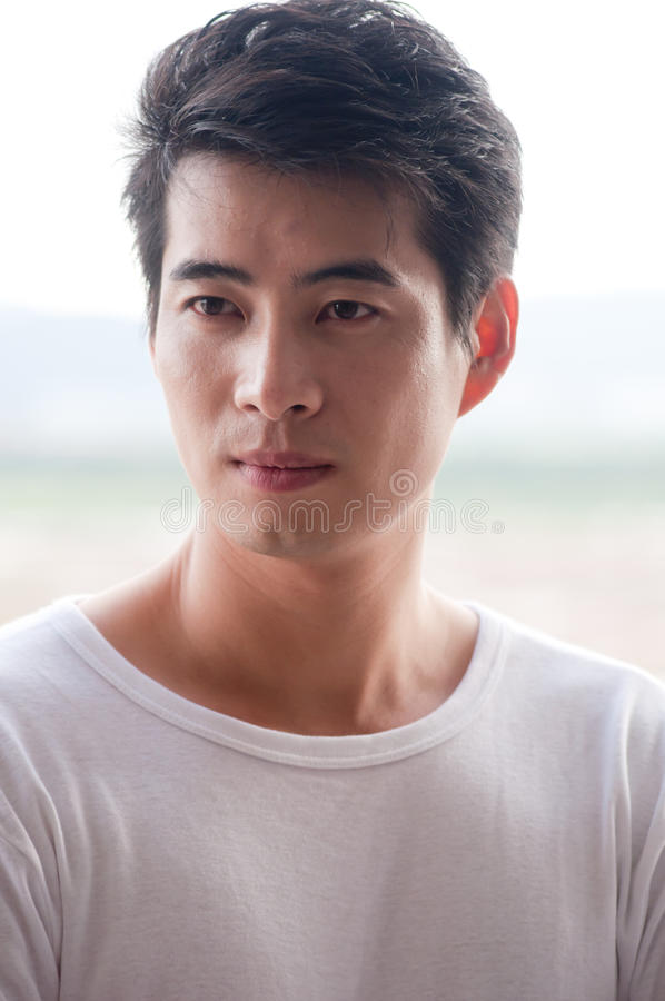 Chinese young man. A young and handsome chinese man wear white t-shirt royalty free stock images