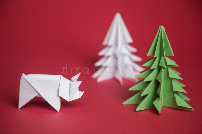 Chinese Zodiac Sign Year of Pig. green origami paper tree and white pig symbol of 2019, on a red background, free space for text,. Minimalism. Happy New Year stock image