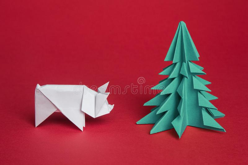 Chinese Zodiac Sign Year of Pig. green origami paper tree and white pig symbol of 2019, on a red background, free space for text,. Minimalism. Happy New Year stock photos