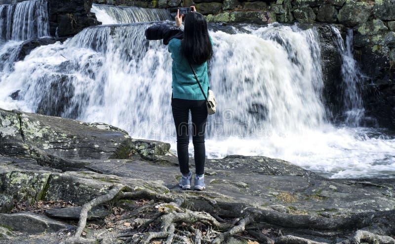 Chinesin, die Fotos des Wasserfalls macht lizenzfreies stockbild