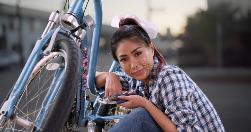 Chinesin, die ihrem Fahrrad einen schnellen Tuneup gibt lizenzfreies stockbild