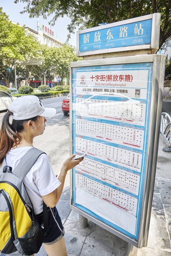 Chinesin mit Rucksack überprüft den Zeitplan an der Bushaltestelle in im Stadtzentrum gelegenem Guilin stockfotos