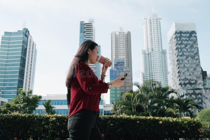 Chinesin mit Telefon-gehendem und trinkendem Kaffee lizenzfreies stockfoto