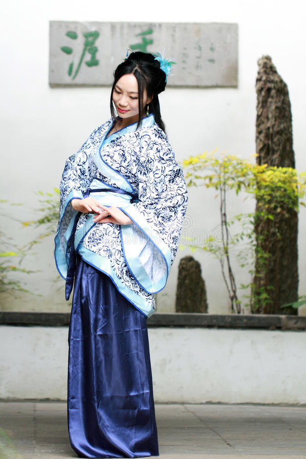 Chinesin in traditionellem blauem und weißem Hanfu-Kleid sitzen nahe bei Bonsais stockfotos