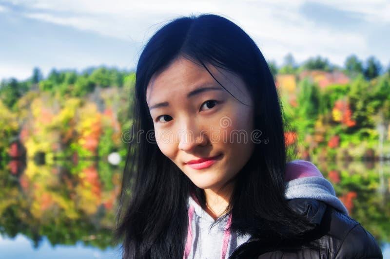Chinesin, welche die Kamera mit Herbstlaubhintergrund betrachtet stockfotos