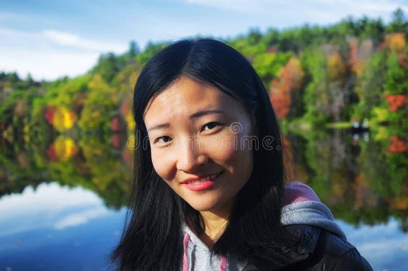 Chinesin, welche die Kamera mit Herbstlaubhintergrund betrachtet lizenzfreie stockfotos