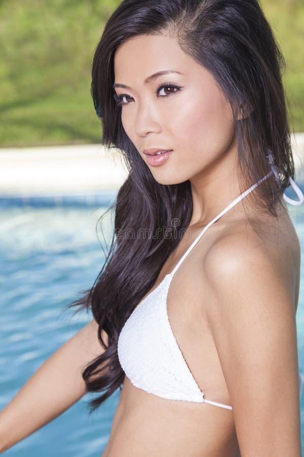 Chinesische asiatische Frau im Bikini durch Swimmingpool lizenzfreie stockfotos