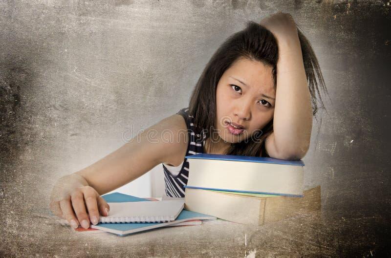 Chinesische asiatische Studentenfrau der Junge bohrte recht das müde und überarbeitete Lehnen auf dem Schulbuchstudieren stockbilder