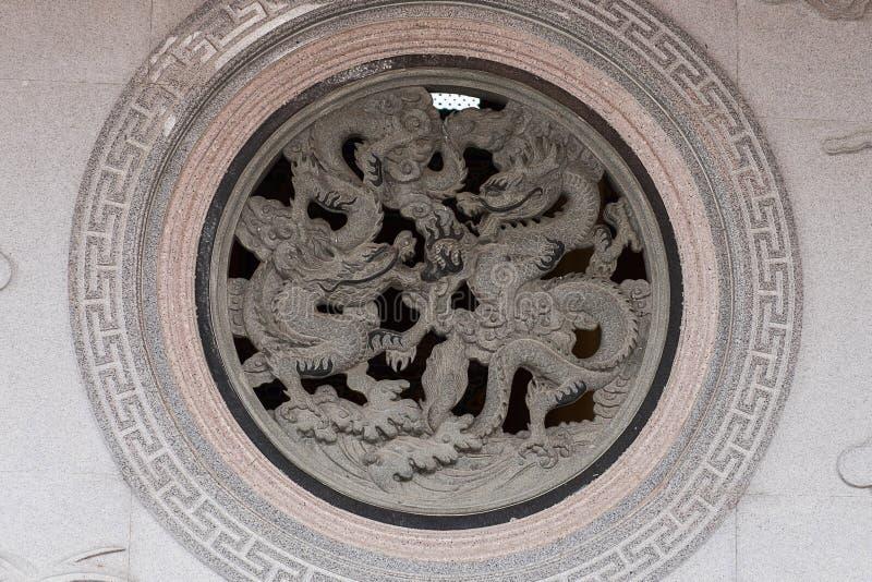 Chinesische Drachen geschnitzt auf Steinwand stockbilder