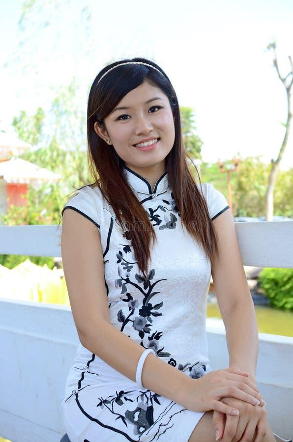 Chinesische Frau tragendes weißes cheongsam stockfotos