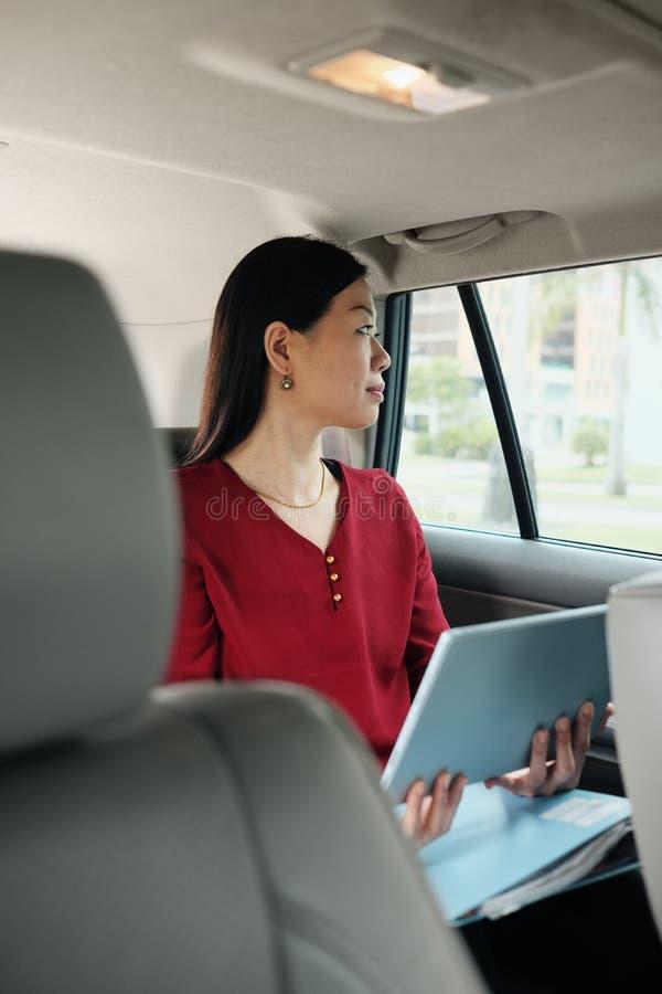 Chinesische Geschäftsfrau, die im Taxi geht zu arbeiten arbeitet lizenzfreies stockfoto