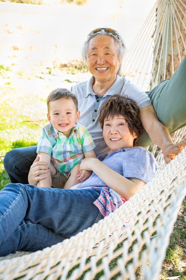 Chinesische Großeltern in der Hängematte mit Mischrasse-Baby lizenzfreie stockfotos