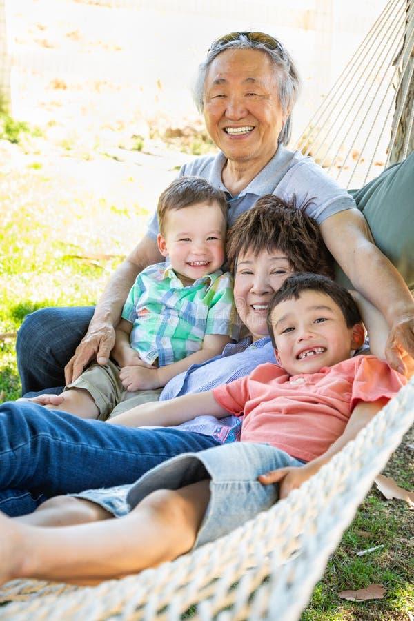 Chinesische Großeltern in der Hängematte mit Mischrasse-Kindern lizenzfreie stockfotos