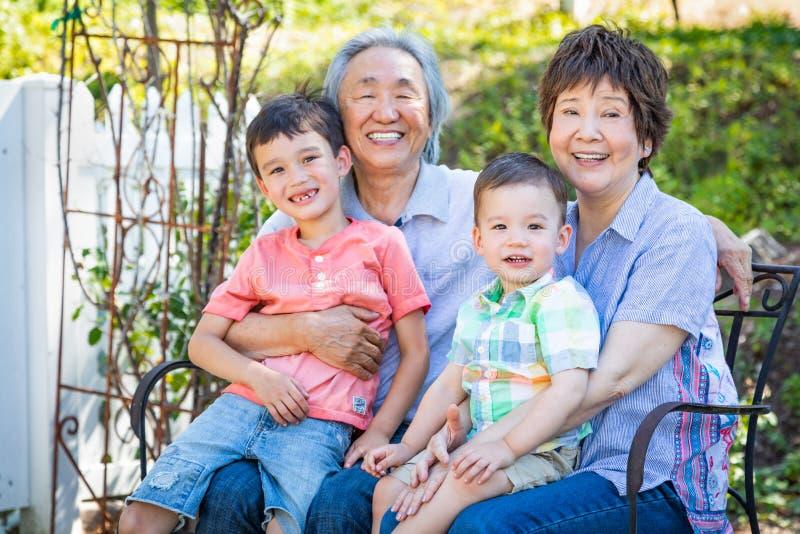 Chinesische Großeltern und Mischrasse-Kinder sitzen auf Bank draußen lizenzfreie stockbilder