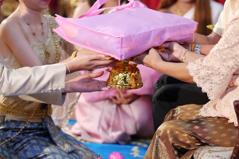 Chinesische Hochzeits-Tee-Zeremonie Braut und Bräutigam, die Geschenk zum Ältesten geben Selektiver Fokus und flache Schärfentief lizenzfreie stockfotografie