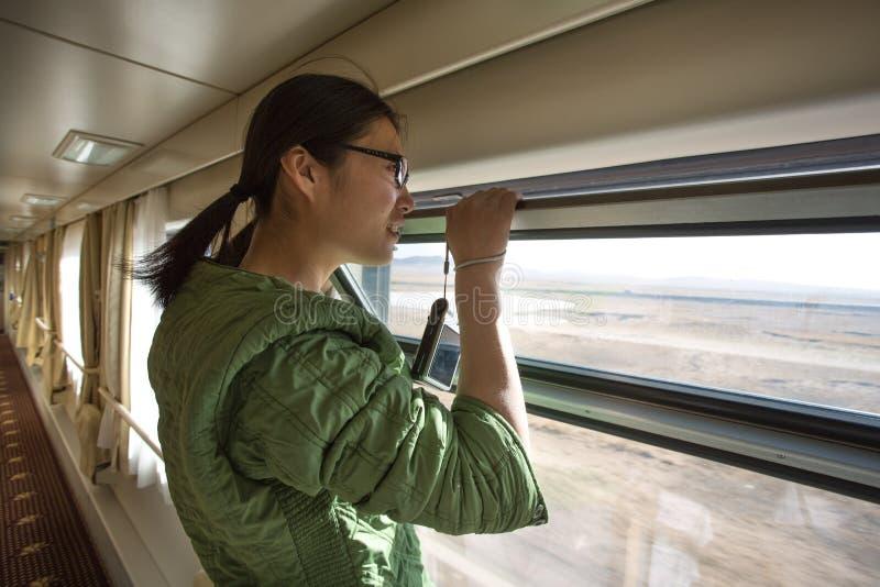 Chinesische junge Frau, die durch ein offenes Fenster im Zug schaut lizenzfreie stockfotos