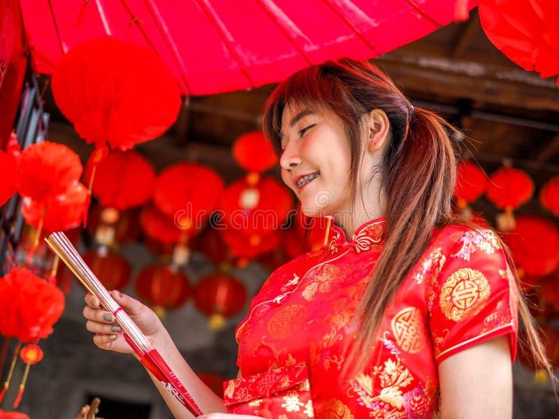 Chinesische junge Frau mit der Traditionskleidung, die Räucherstäbchen hält, verärgern, Chinesisches Neujahrsfest lizenzfreie stockfotos