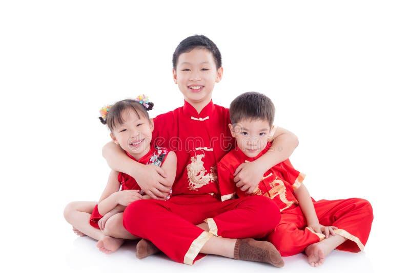 Chinesische Kinder, die traditionelles Kostümsitzen und -lächeln auf dem Boden tragen lizenzfreies stockfoto