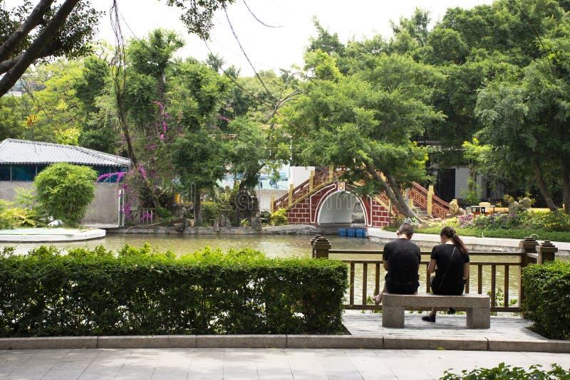 Chinesische Liebhaberleute sitzen auf Steinbank und der Entspannung im Garten an Zhongshan-Park in Shantou-Stadt oder in Swatow-S stockfoto