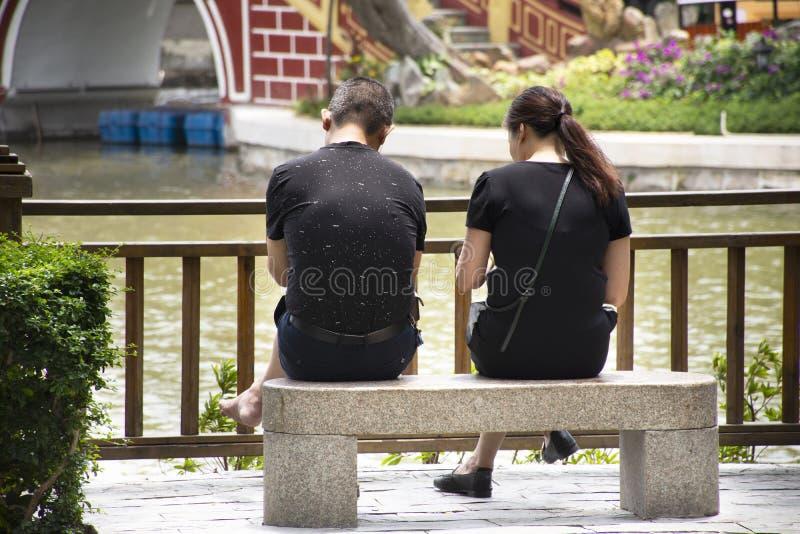 Chinesische Liebhaberleute sitzen auf Steinbank und der Entspannung im Garten an Zhongshan-Park in Shantou-Stadt oder in Swatow-S lizenzfreie stockfotografie