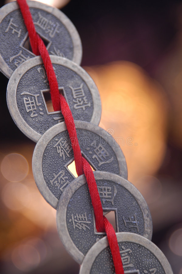Chinesische Münzen auf Zeichenkette stockfotografie