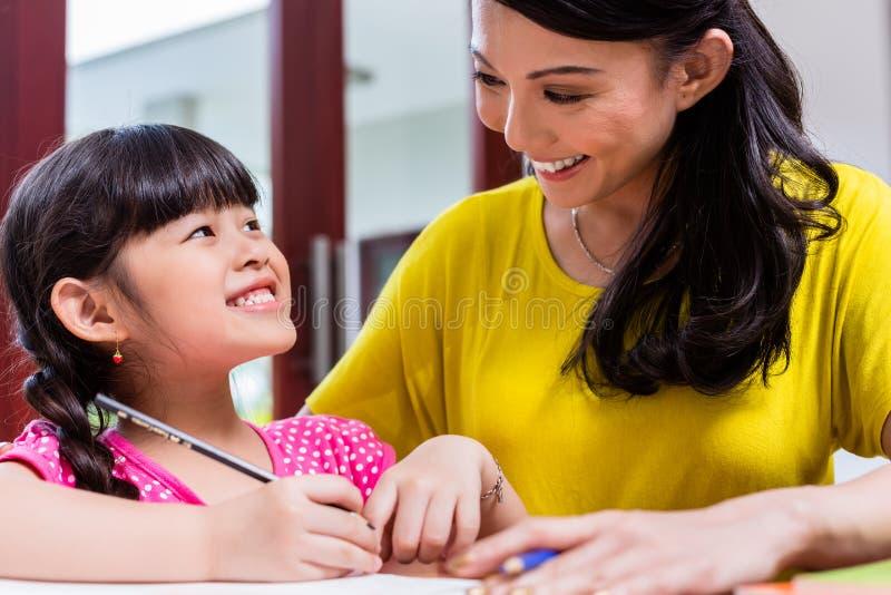 Chinesische Mutter, die ihr Kind homeschooling ist stockfotografie