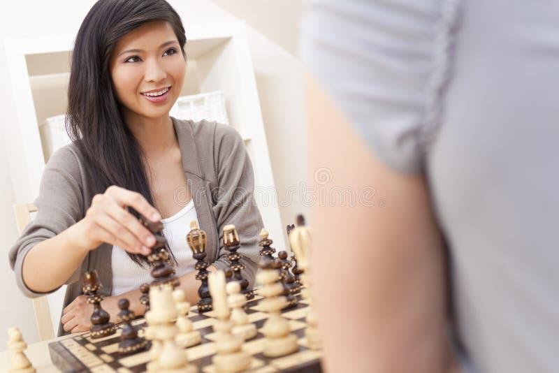 Chinesische orientalische asiatische Frau, die Schach spielt stockbilder