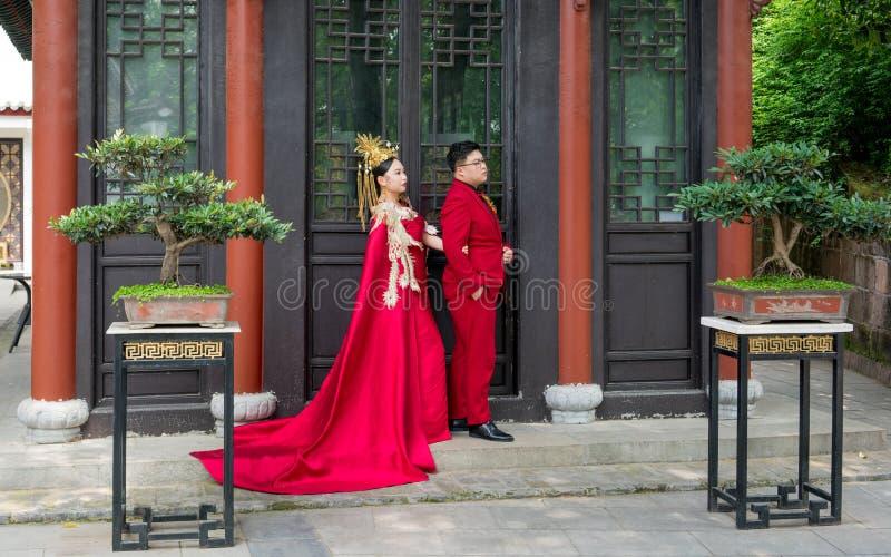 Chinesische Paare mit den traditionellen roten Kostümen, die für Heiratsbilder an Qingchuan-Pavillon in Wuhan China aufwerfen lizenzfreie stockfotografie