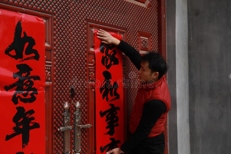 Chinesische ` s neues Jahr des Mannbeitrags Rollen, Frühlingsfestdistichons und Mars an der roten Tür in China lizenzfreie stockbilder