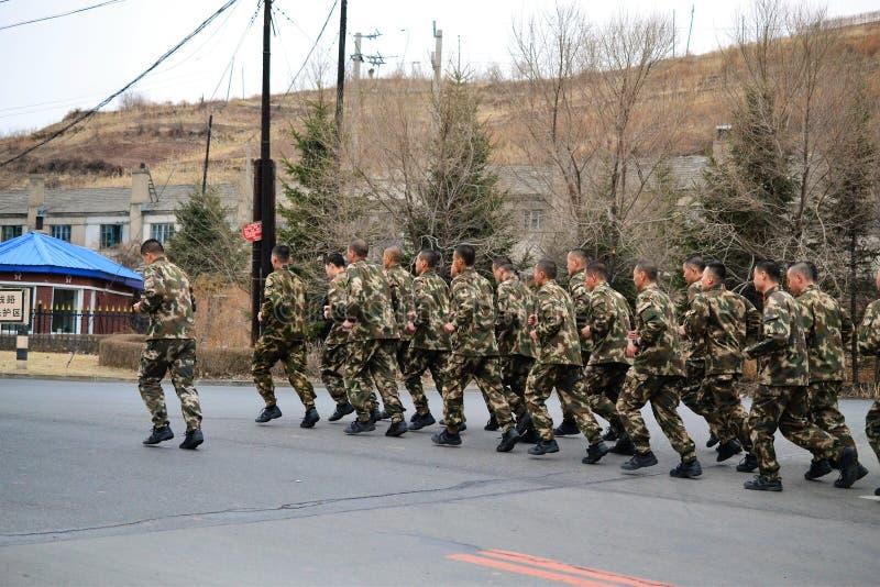 Chinesische Soldaten, die in Tumen-, Jilin-Provinz, Grenze Chinas, Fluss zwischen Nordkorea und China laufen lizenzfreies stockbild