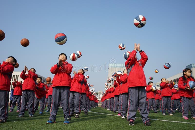 Chinesische Studenten tun Basketball Gymnastik lizenzfreie stockbilder