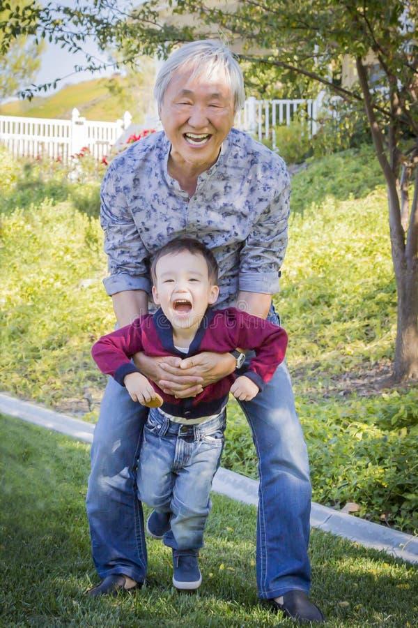 Chinesischer Großvater, der Spaß mit seinem Mischrasse-Enkel draußen hat lizenzfreie stockfotos
