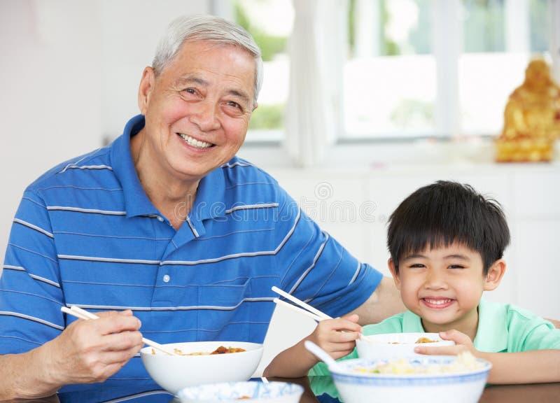 Chinesischer Großvater und Enkel, die Mahlzeit isst stockfoto