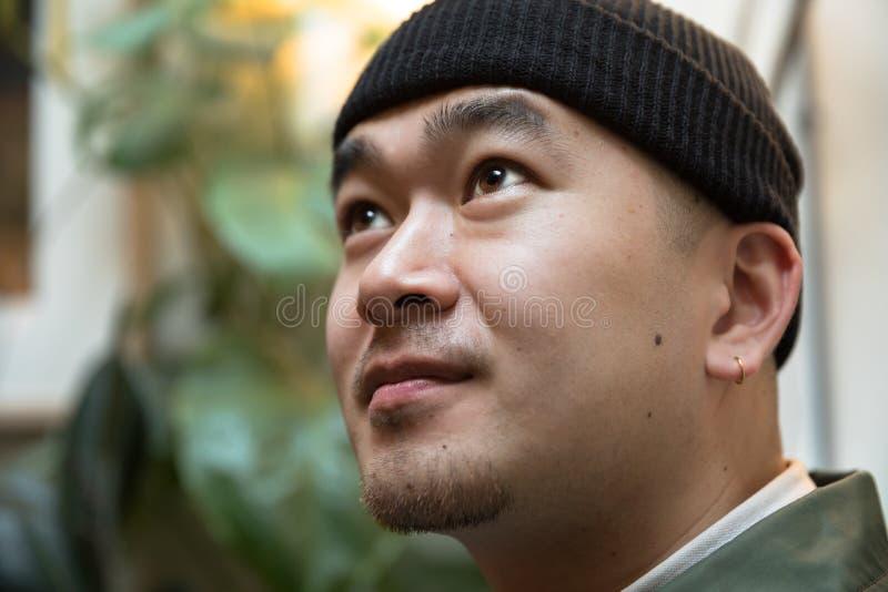 Chinesischer junger Mann mit Ohrring gegen Grünpflanzehintergrund lizenzfreie stockbilder