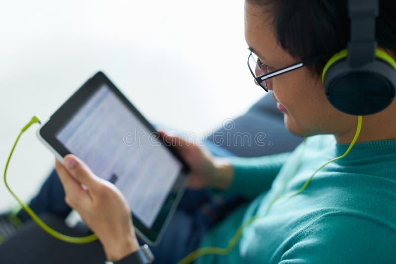 Chinesischer Mann mit grünen Kopfhörern hört Podcast-Tablet-PC lizenzfreie stockfotos