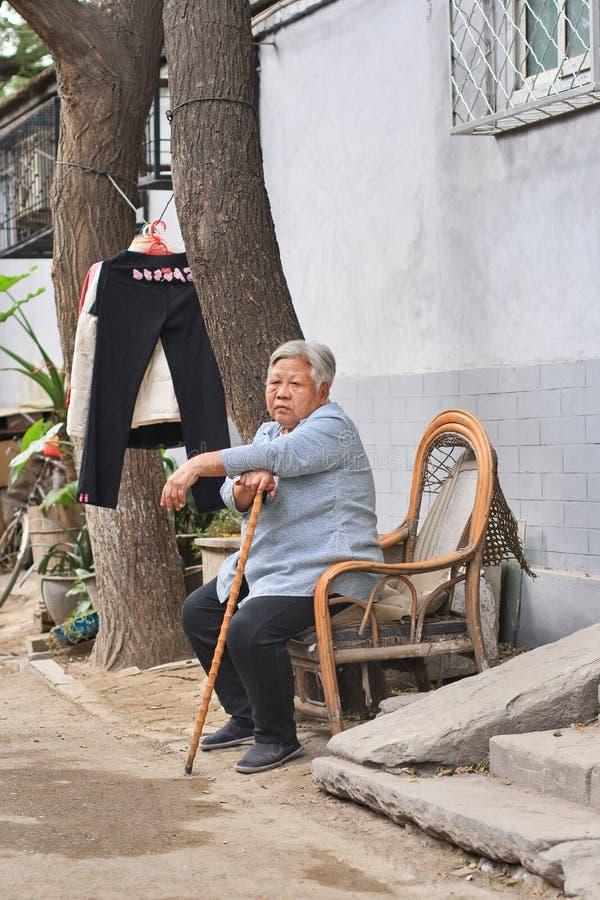 Chinesischer weiblicher Senior sitzen draußen in einem hutong, Peking, China stockfoto