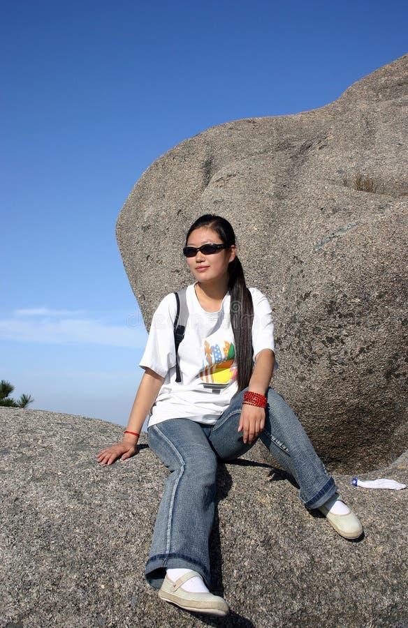 Chinesisches Mädchen, das auf Felsen sich entspannt stockfoto