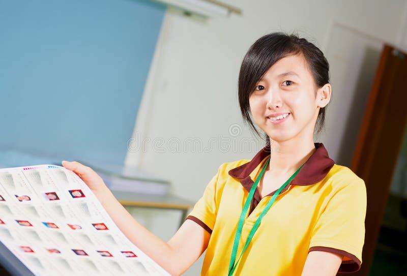 Chinesisches Mädchen, das ein Prüfen im Druckhaus hält lizenzfreie stockbilder