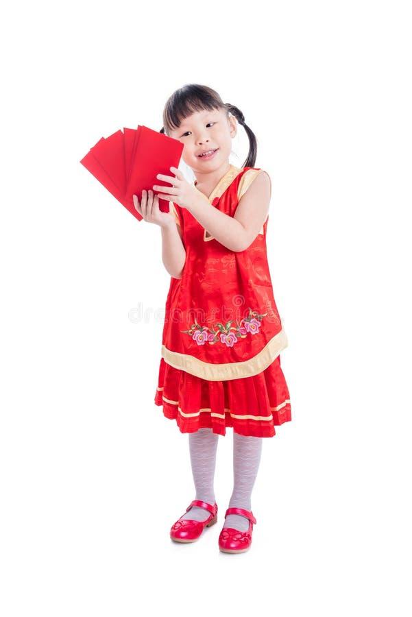 Chinesisches Mädchen im rote Farbtrachtenkleid, das rotes Paketgeld hält stockbild