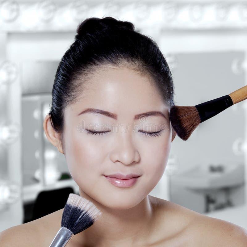 Chinesisches Mädchen wenden Make-upbürsten an stockbild