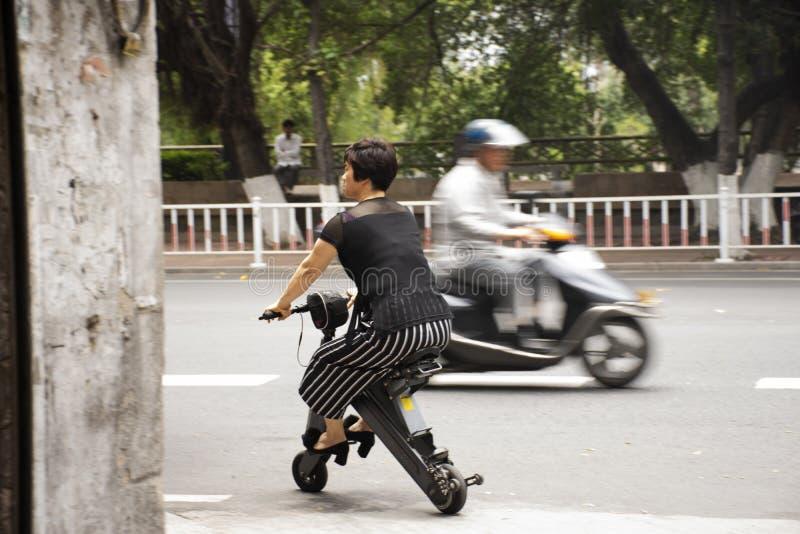 Chinesisches Volk fährt und fährt neues Innovationsrollerfahrrad rad, das auf der Straße im alten Stadtbereich bei Shantou oder b stockfoto