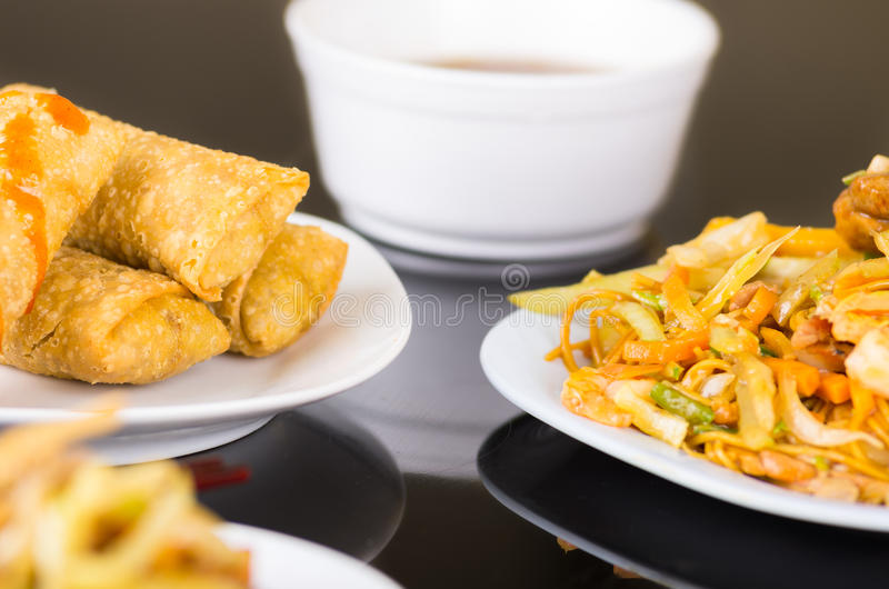 Chinesse food, spring rolls and noodles with vegeatbles served on a white dishes royalty free stock image