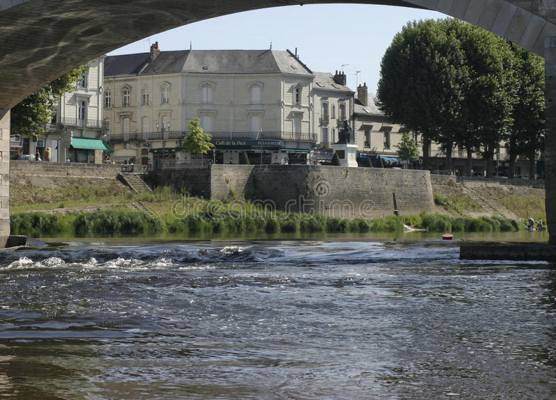 Chinon on the Vienne river in France. View from the bank under the bridge towards the corner cafe and monument royalty free stock photography