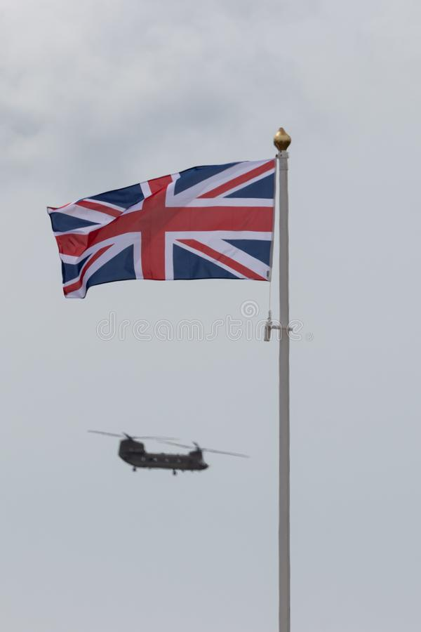 A chinook helicopter flying behind a union jack flag on a flag pole. A chinook helicopter flying behind a union jack flag or a british flag on a flag pole stock image